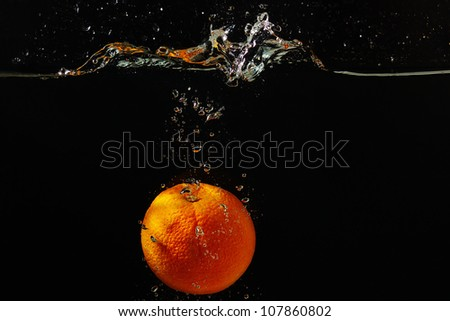 Fresh orange falling into the water with a splash on a black background closeup