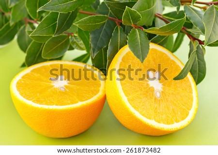 Fresh orange halves on modern green hardboard. - stock photo