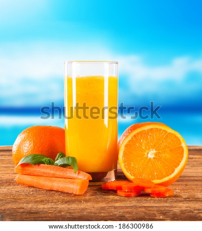 Fresh orange juice drink with fruits and blue sky on wooden table - stock photo