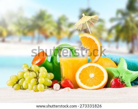 Fresh orange juice, fruits on sand with blue sky background, summer concept  - stock photo
