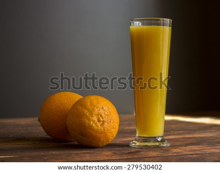 Fresh orange juice in a glass on a wooden table with oranges - stock photo