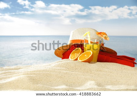fresh orange juice in glass and hat and red towel and sand
