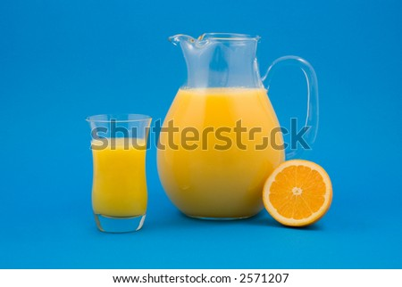 Fresh Orange Juice in Glass and Pitcher with Half-cut Orange Isolated on Blue Background - stock photo