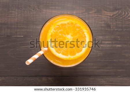Fresh orange juice in glass on wooden background. - stock photo