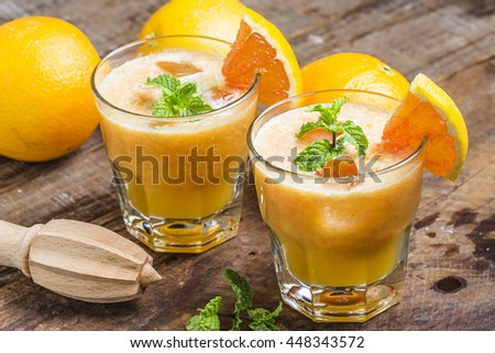 Fresh orange juice, mint and ice on dark background, top view