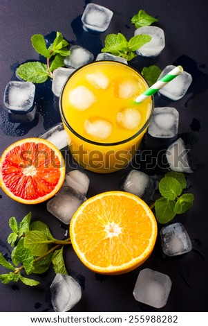 Fresh orange juice,  mint and ice on dark background, top view, copy space - stock photo