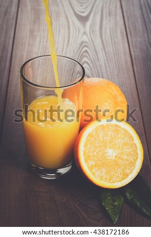 fresh orange juice pouring into glass on the brown wooden table - stock photo