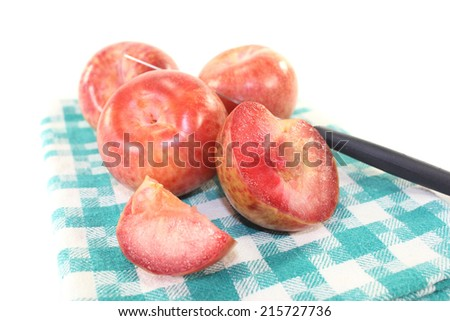 fresh orange-red pluots on a light background
