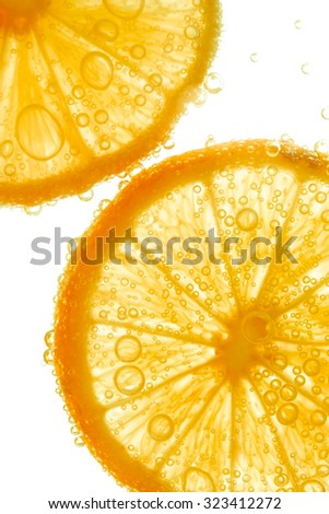 Fresh orange slice in water with bubbles on white background - stock photo