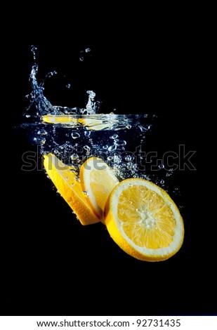 Fresh orange slice splashing into water - stock photo