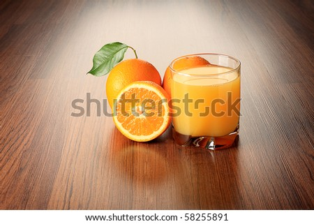 Fresh oranges and glass of orange juice on a table.