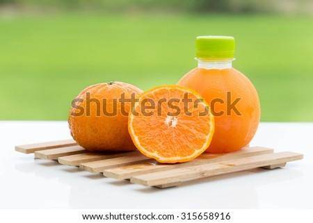 Fresh oranges and orange juice bottle. Natural morning light - stock photo