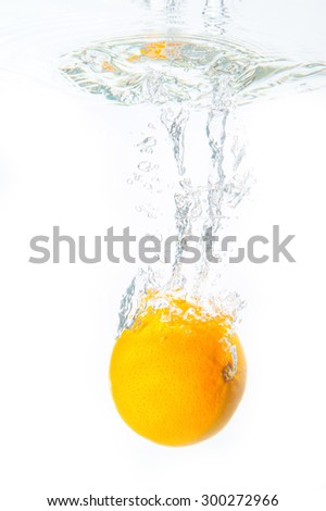 Fresh oranges dropped into water