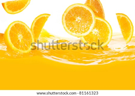 Fresh oranges falling in juice on white background - stock photo