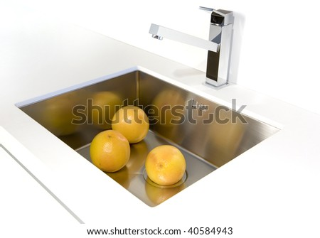 Fresh oranges in the sink on white table - stock photo