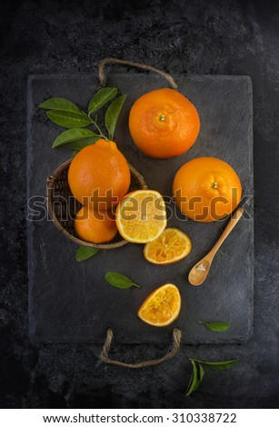 Fresh oranges on rustic black background. Overhead view shot. Stylized food. - stock photo
