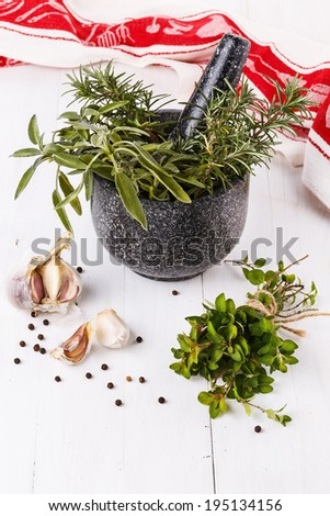 Fresh oregano, sage and rosemary in a gray granite mortar with garlic and black pepper over white wooden background - stock photo