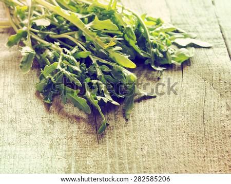 Fresh organic arugula on raw wooden background. Grunge style. - stock photo