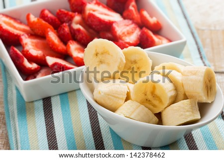 Fresh organic  banana and strawberry in bowls on wooden background. Selective focus. Rustic style. Healthy eating. - stock photo