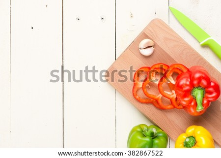 Fresh organic bell peppers on a wooden board - stock photo