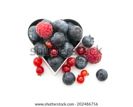 fresh organic berries in heart shape isolated on white background
