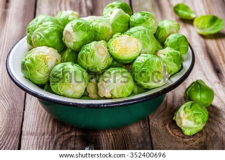 Fresh organic Brussels sprouts in a bowl on a wooden table - stock photo