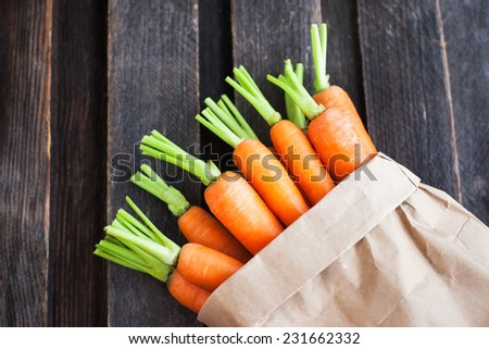 Fresh organic carrots in a paper bag on wooden background - stock photo