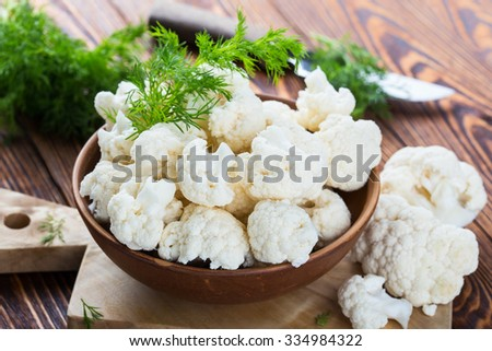 Fresh organic cauliflower cut into small pieces in ceramic bowl on wooden background - stock photo