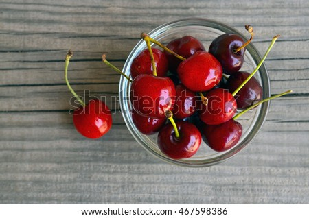 Fresh organic cherries berries in glass bowl on old wooden background.Selective focus.Top view.