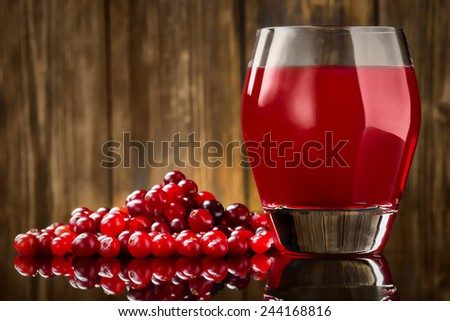 Fresh Organic Cranberry Juice against a wooden background - stock photo
