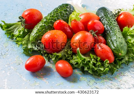 Fresh organic cucumbers, tomatoes, lettuce, rich in vitamins and minerals on a blue old table. Selective focus - stock photo