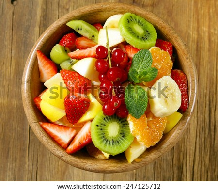 Fresh organic fruit salad (kiwi, strawberry, banana, currant, apple) - stock photo