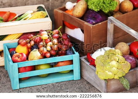 Fresh organic fruits and vegetables in wooden boxes outdoors - stock photo