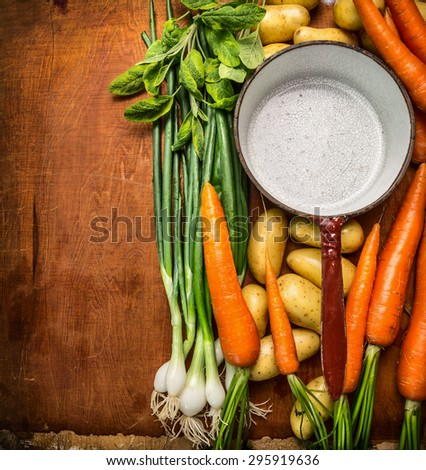 Fresh organic garden vegetables around empty old cooking pan on wooden background, top view, place for text - stock photo