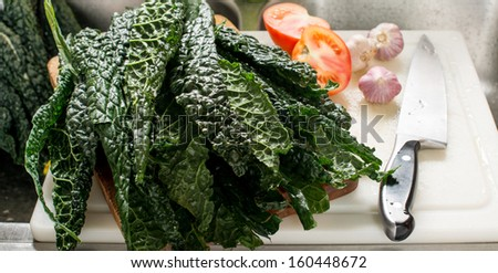 Fresh Organic Kale Leaves on Wooden Cutting Board with Knife - stock photo