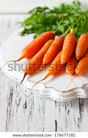 Fresh organic kitchen garden carrots on vintage wooden plate close-up. - stock photo