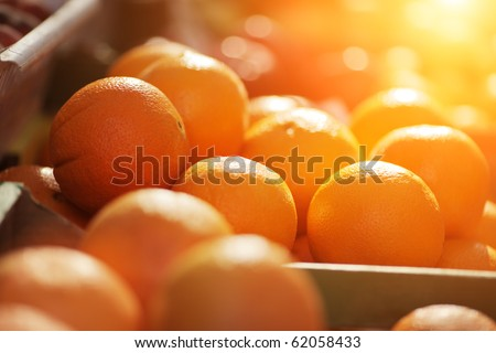 Fresh organic oranges on display on sunny day. Shallow DOF. - stock photo
