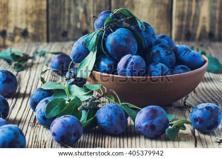 Fresh organic plums in ceramic bowl on  rustic wooden table - stock photo
