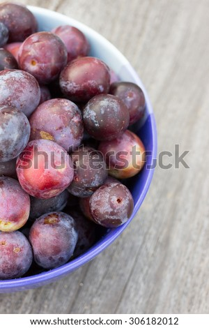 Fresh Organic Plums on Rustic Wooden Background. Retro Filter Effect. Vintage Style Harvest Background. Toned image with selective focus.
