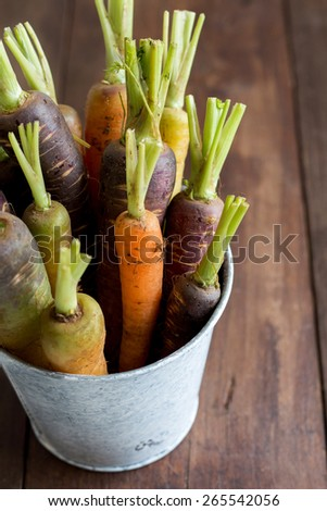 Fresh organic rainbow carrots in a bucket on a wooden table