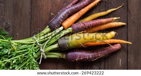Fresh organic rainbow carrots on a wooden table - stock photo