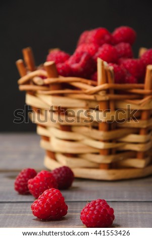 Fresh organic ripe raspberry in a wicker basket on the wooden background. Selective focus - stock photo