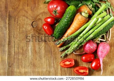 fresh organic spring vegetables (tomato, asparagus, carrots, cucumber, radish) - stock photo
