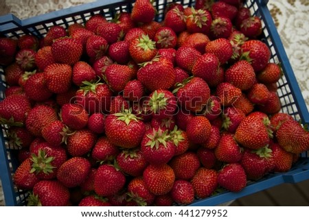 Fresh organic strawberries in the blue plastic box. White vintage table. Top view