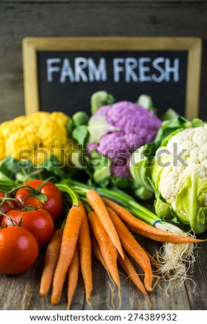 Fresh organic vegetable in season on old farm table. - stock photo