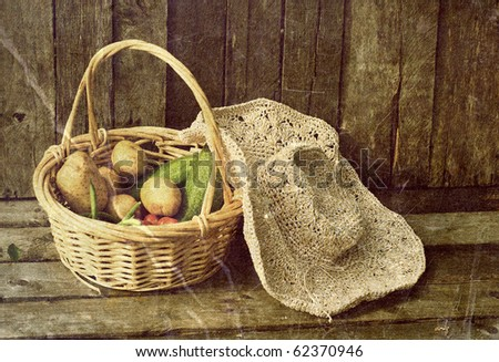 Fresh  organic vegetables and a straw hat on a grunge wood background.  Grunge textured. - stock photo