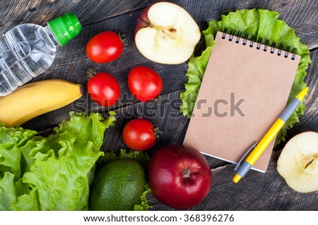 Fresh organic vegetables and fruits. Lettuce, avocado, apple, banana, water bottle, open blank notebook and pen on wooden background. Healthy food and healthy life concept. Top view - stock photo