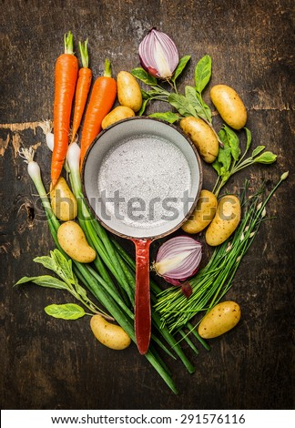 Fresh organic vegetables and herbs around old empty cooking pot on rustic wooden background, top view composing, copy space - stock photo