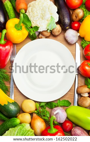 Fresh Organic Vegetables Around White Plate with Knife and Fork /  Vertical Composition - stock photo