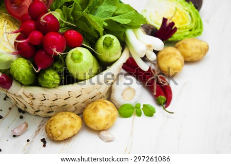 Fresh organic vegetables in a basket with spices on a white wooden table - stock photo